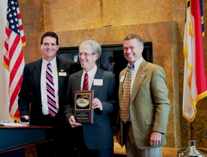 Mickey Duvall (left) and Gary D. Blevins (right) with Ed Rosenbeg (center) holding award